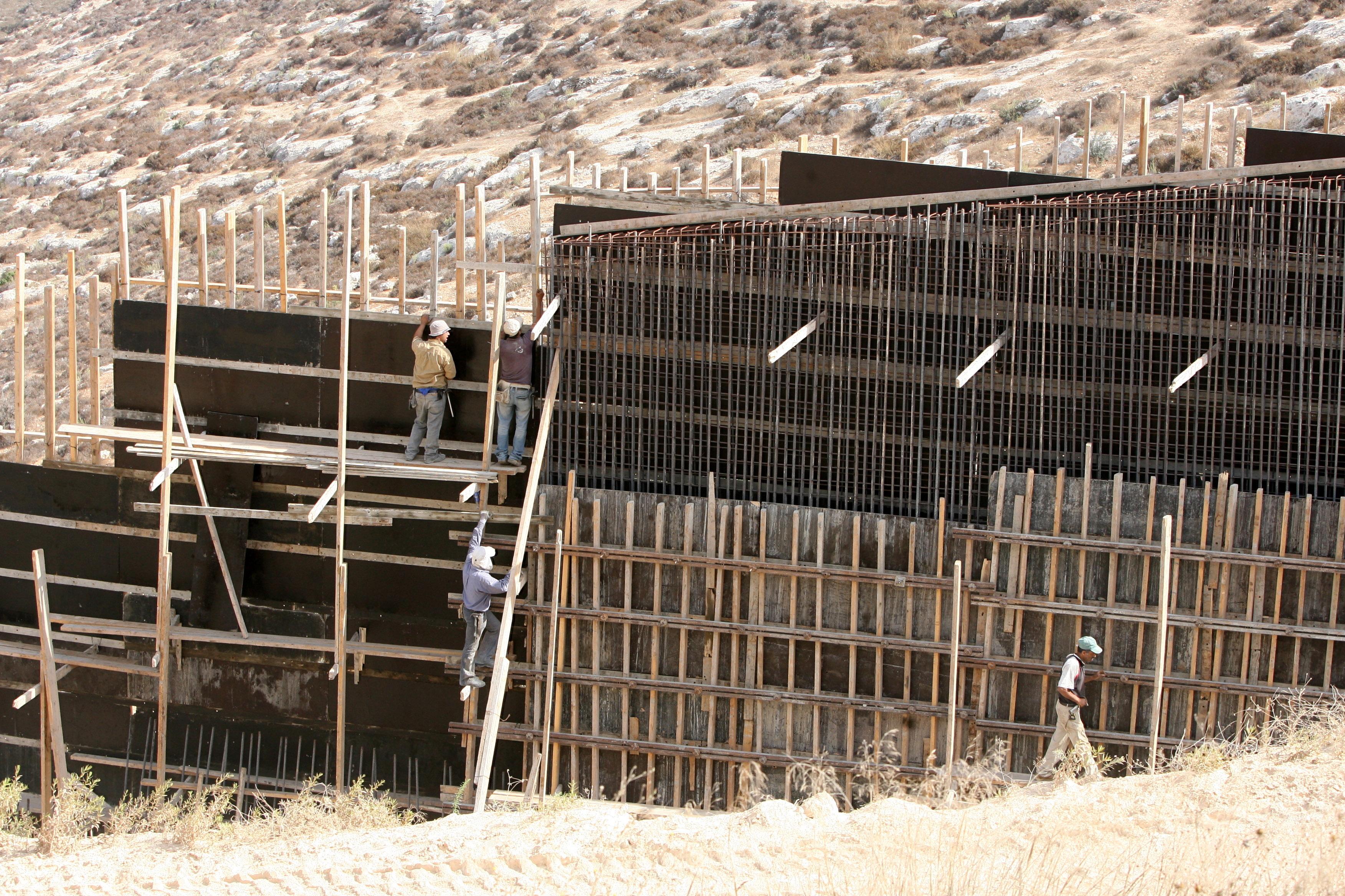 Cтроительство спорного израильского разделительного барьера возле деревни на Западном берегу. Фото: EPA