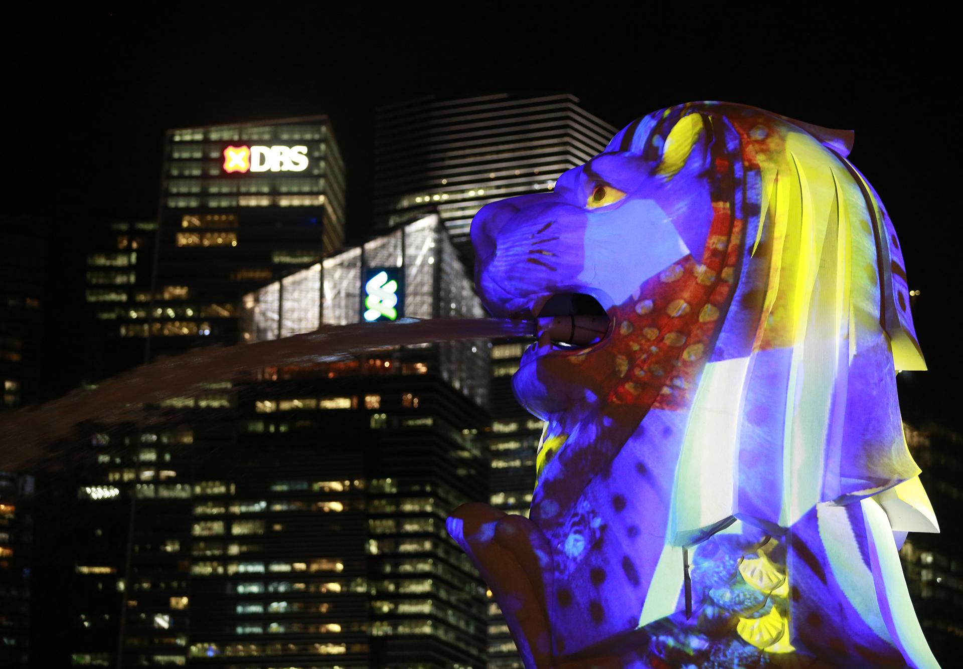 Глава статуи Мерлион освещается видеопроекцией под названием «Тело моря» во время фестиваля Light Marina Bay в Сингапуре, 01 марта 2017 года. EPA / WALLACE WOON