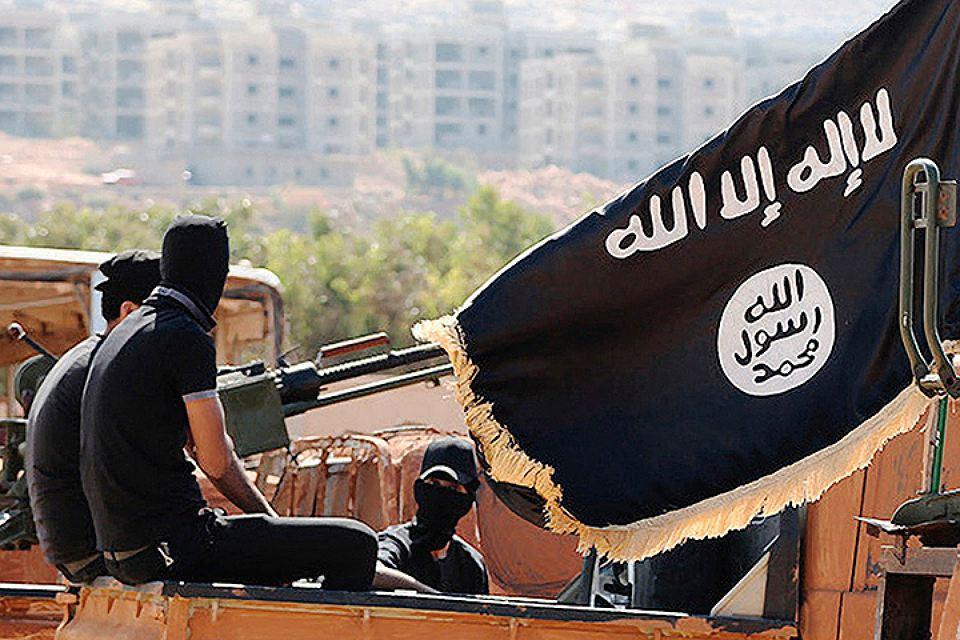 """Флаг ИГ: арабская вязь с первой частью """"шахады"""", свидетельством о вере в Единого Бога Аллаха, и печать пророка Мохаммеда снизу"""