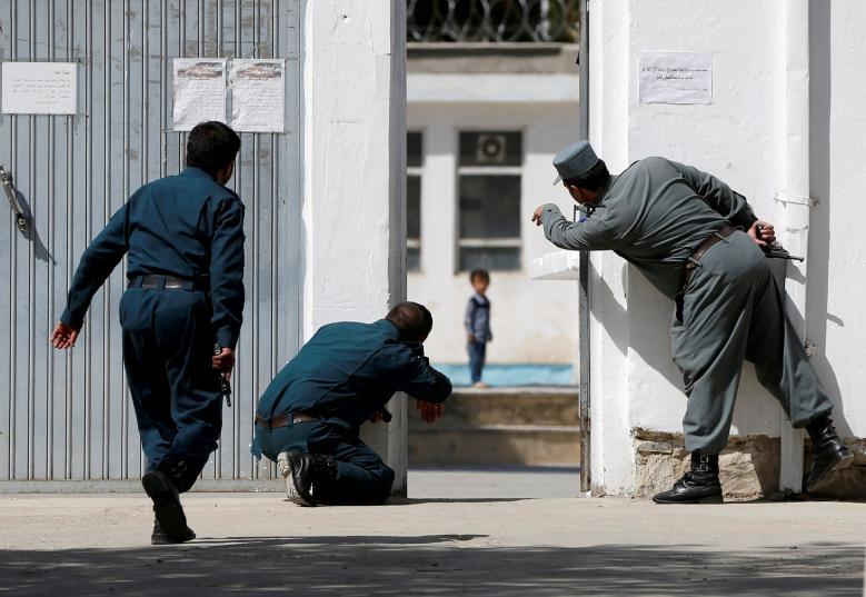 Афганские полицейские пытаются спасти ребенка на месте нападения террористов-смертников