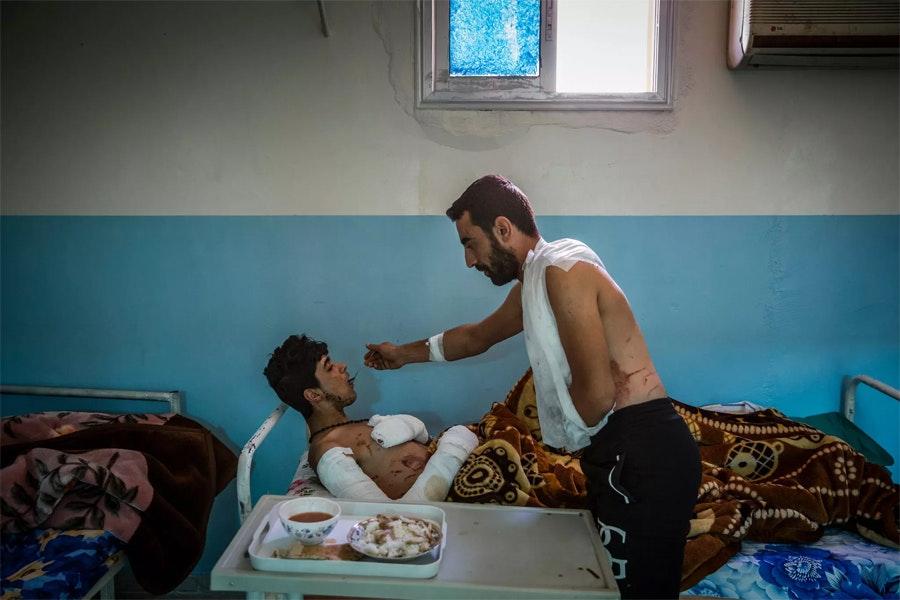 Раненный сирийский солдат кормит своего товарища / Фото: Айвор Прикетт
