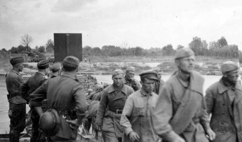 Первые советские военнопленные под наблюдением немецких солдат направляются из Украины на запад по мосту через реку Сан у города Ярослав (сейчас находится в Польше)