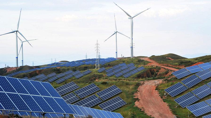 Солнечные батареи и ветровые турбины на склоне горы в деревне Шэньцзин, Китай / VCG / Big Think