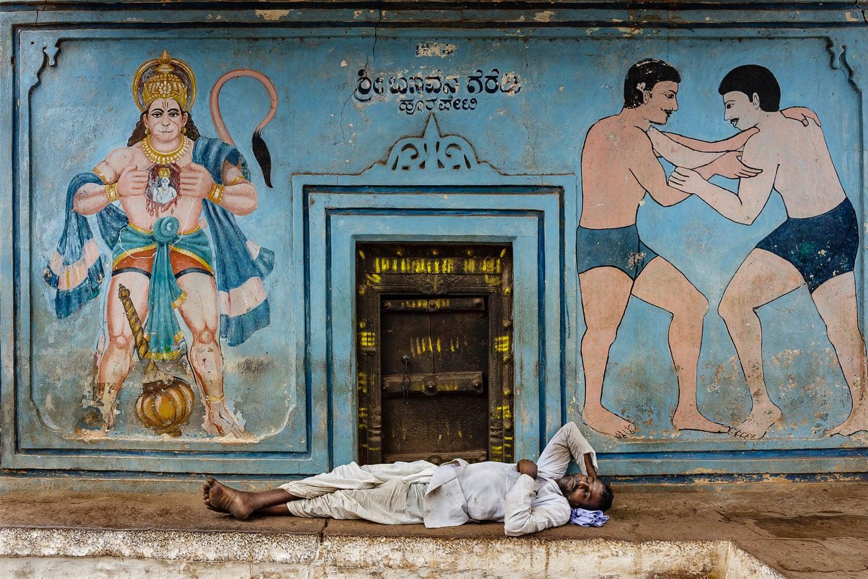 Мужчина отдыхает у входа в зал традиоцонной борьбы кушти в городе Бадами, Индия