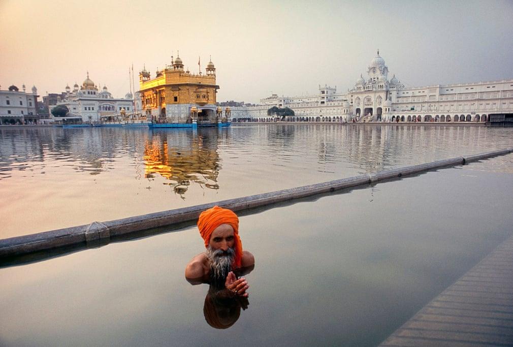 Сикх-пилигрим совершает ритуальное омовение в бассейне около Золотого Храма в городе Амритсар (Пенджаб, Индия).