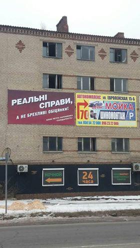Предвыборная политическая реклама прикрывает разбитые окна на домах, г. Константиновка